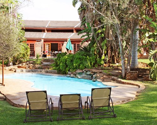 Outdoor swimming pool with chaise lounge chairs alongside a unit at Gethlane Lodge.