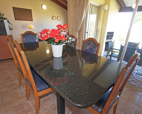 A well furnished dining area with a television and patio.