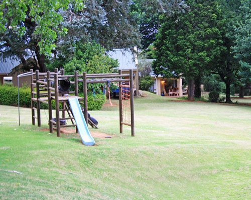 A playscape alongside a manicured lawn.