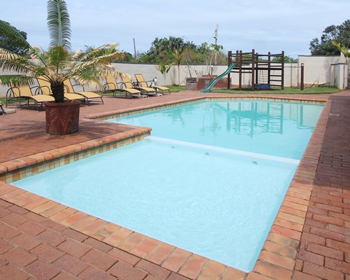 Outdoor swimming pool with chaise lounge chairs and kids playscape.