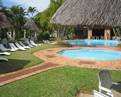 An outdoor swimming pool and hot tub with thatched sunshades and chaise lounge chairs.