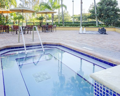 An outdoor swimming pool with patio furniture and sunshades.