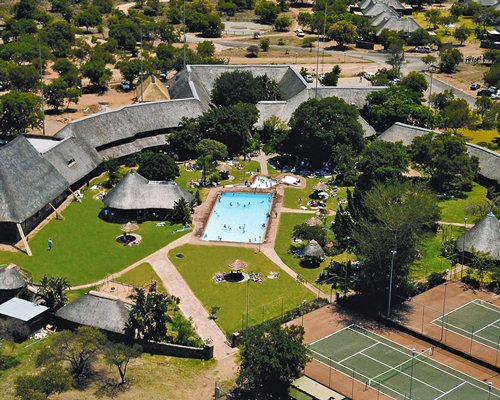 An aerial view of outdoor tennis courts and the swimming pool alongside the resort.