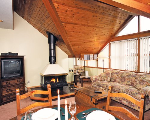 A well furnished living and dining area with a television and fire at the fireplace.