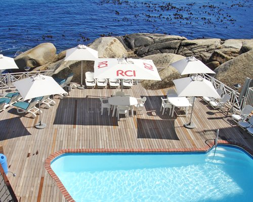 An outdoor swimming pool with sunshades patio furniture and chaise lounge chairs alongside the ocean.