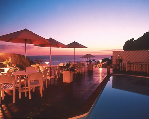 A well furnished outdoor dining area with sunshades alongside the beach at night.