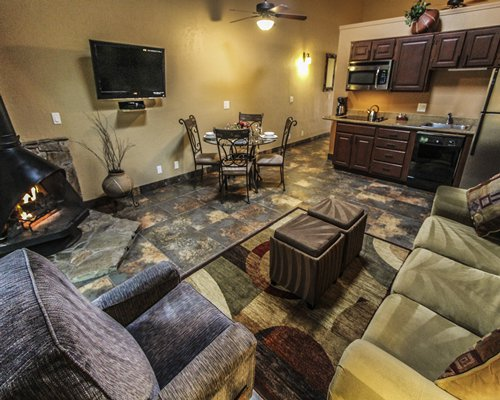 An open plan living room with television and fire in the fireplace dining area and kitchen.