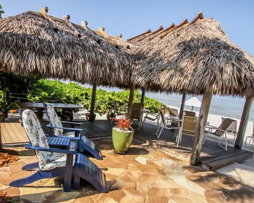 A view of patio furniture and thatched sunshades alongside the ocean.