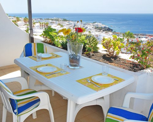 A balcony with dining setup alongside the beach.