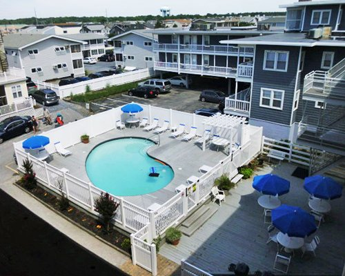 Outdoor hot tub with chaise lounge chairs and sunshades alongside multiple unit balconies and parking lot.