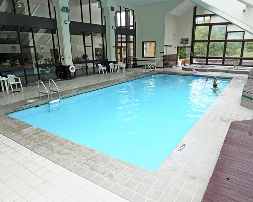 An indoor swimming pool with hot tub patio and an outside view.