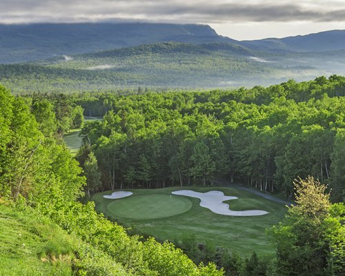 A well maintained golf course surrounded by wooded area alongside the mountains.