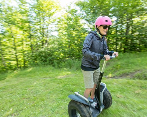 A man riding a hoverboard in the wooded area.
