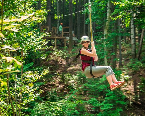 A woman zip lining in a wooded area.