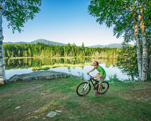 A man riding bike alongside the lake surrounded by wooded area.