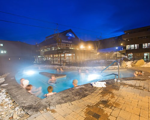 View of people at an outdoor hot tub alongside units at Sugarloaf Mountain Hotel.