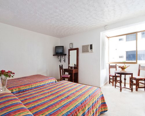 A well furnished bedroom with two beds and a television alongside a dining area.