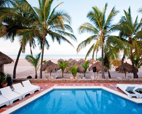Outdoor swimming pool with chaise lounge chairs palm trees and thatched sunshades alongside the beach.