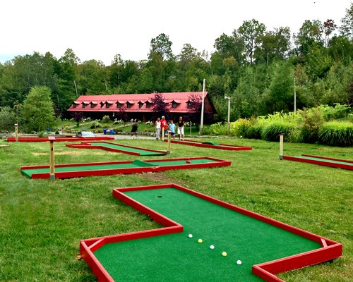 People at an outdoor recreation area with putt putt golf course surrounded by wooded area.