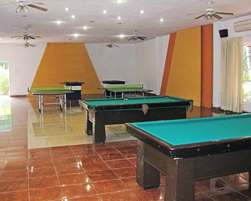 Indoor recreation room with pool tables and ping pong.