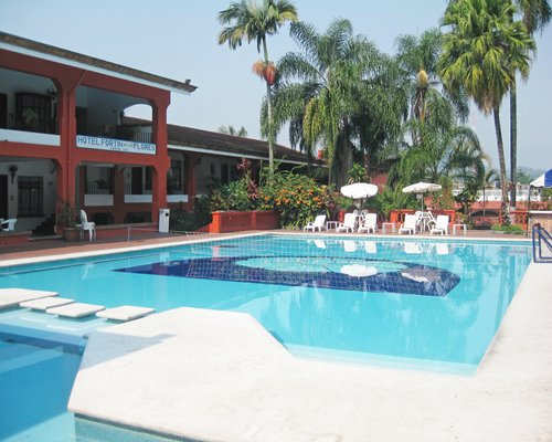 Large outdoor swimming pool with chaise lounge chairs sunshades and palm trees.