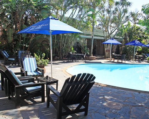 A view of an outdoor swimming pool with patio furniture and sunshades.