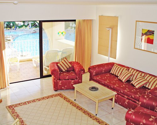 A well furnished living room with pull out sofa and a patio alongside the swimming pool.