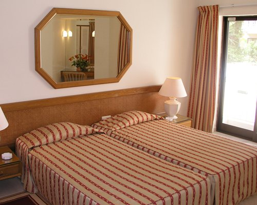 A well furnished bedroom with two beds mirror and an outside view.
