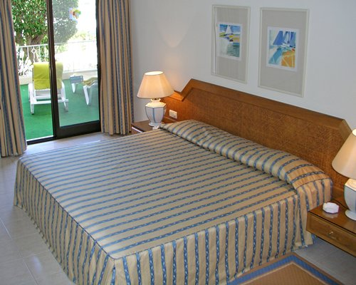 A well furnished bedroom with a king bed and a patio.