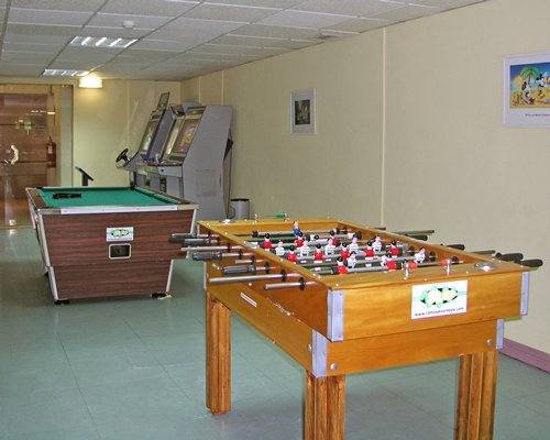 An indoor recreation room with table soccer pool table and arcade game.