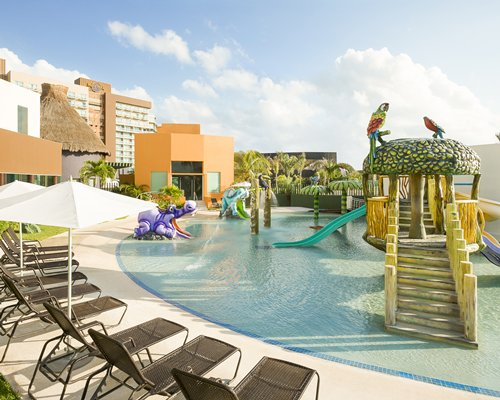 Outdoor kiddie pool with water slides mushroom umbrella fountains and chaise lounge chairs.