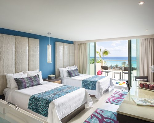 A well furnished bedroom with two queen beds dining area and outdoor patio with ocean view.