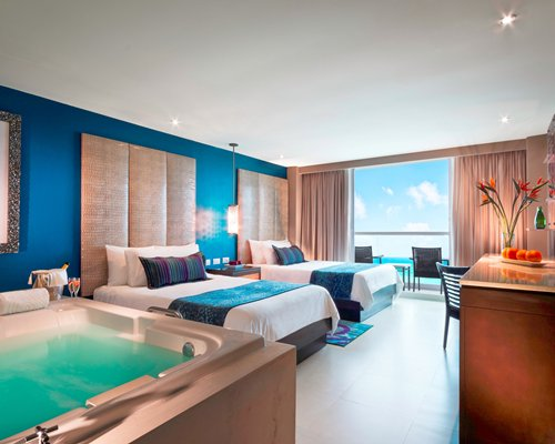 A well furnished bedroom with two beds a hot tub and a balcony.