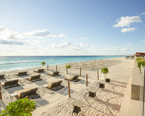A view of chaise lounge chairs at the sea shore.