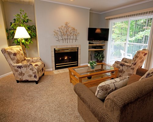 A well furnished living room with a television fire in the fireplace and a balcony.