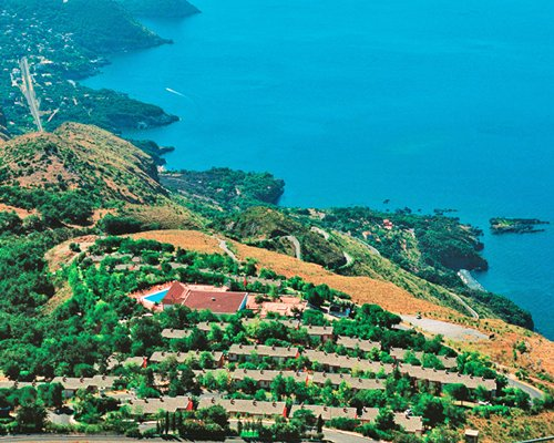 A bird view of the Pianeta Maratea resort surrounded by trees alongside the ocean.