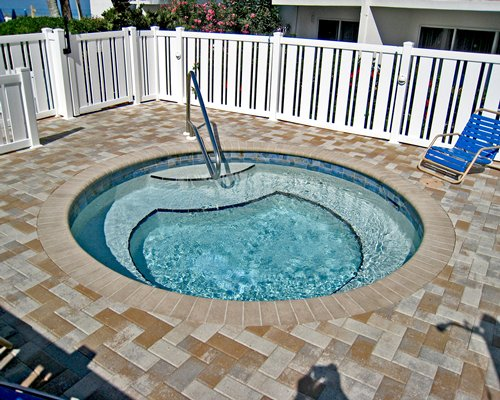 Outdoor hot tub with a chaise lounge chair.