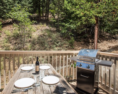 A view of barbecue grill with a wooden dining table surrounded by wooded area.