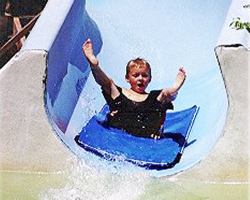 A kid playing in the water slide.