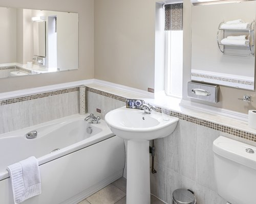 A bathroom with a shower bathtub and single sink vanity.