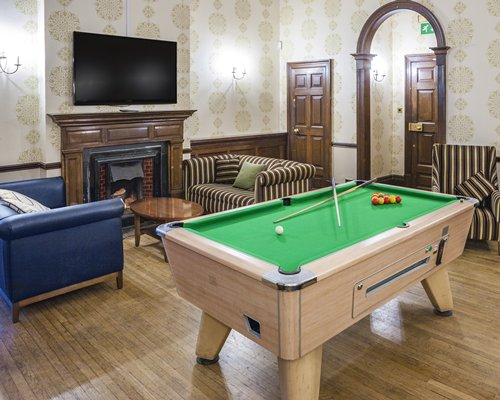 An indoor recreational room with a pool table and television.