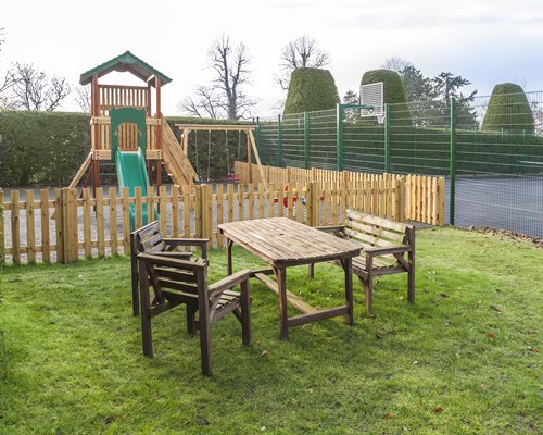 Outdoor kids playscape with patio furniture.