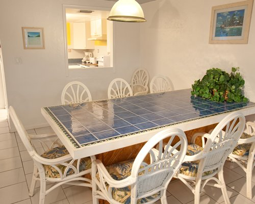 A well furnished dining room alongside a kitchen.