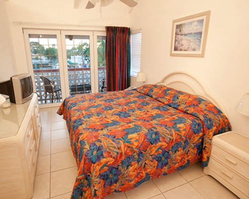 A well furnished bedroom with a television and a balcony with patio.