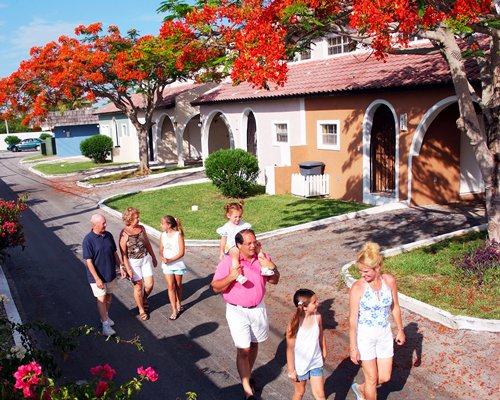 A group of people walking in the pathway alongside the resort units.
