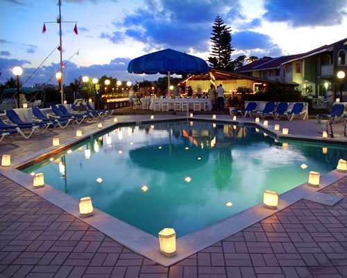 An outdoor swimming pool with chaise lounge chairs and dining area at dusk.