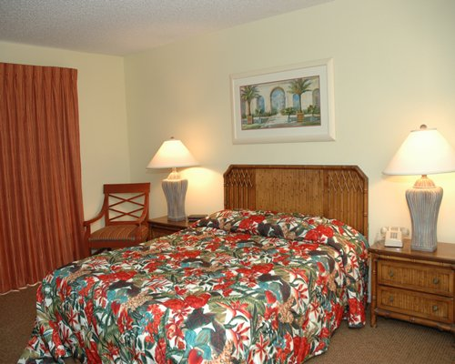 A well furnished bedroom with a queen bed and two lamps.