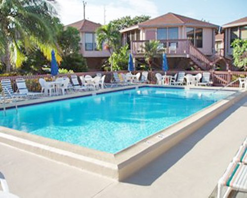 An outdoor swimming pool with chaise lounge and patio furniture alongside resort units.