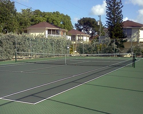An outdoor tennis court surrounded by trees alongside resort units.