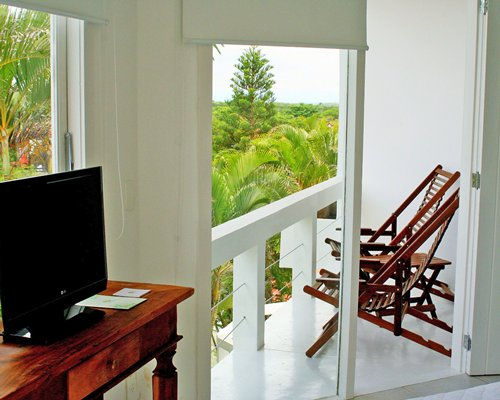A well furnished indoor room with a television and a balcony with patio furniture.